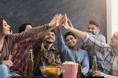 Multiracial friends giving high five together. Multiracial friends giving high five while having party at home royalty free stock image