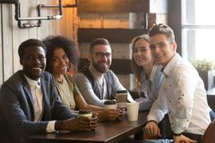 Multiracial friends group looking at camera sitting in cafe, por. Happy multiracial friends group looking at camera having fun in cafe together, young african Royalty Free Stock Photos