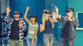 Multiracial friends group playing on vr glasses indoors. Virtual reality concept with young people having fun together. royalty free stock photos