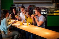 Multiracial friends having fun eating pizza in pizzeria. Royalty Free Stock Images