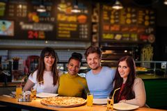 Multiracial friends having fun eating in pizzeria. Royalty Free Stock Image