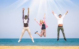 Multiracial friends jumping at the beach. Three multiracial friends jumping at the beach - Concept of happyness and friendship against racism Royalty Free Stock Image