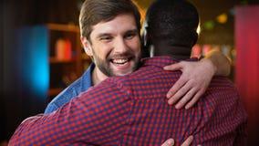 Multiracial friends meeting in pub, making greeting gesture and hugging, weekend. Stock footage stock footage