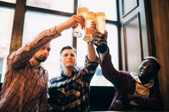 Multiracial friends men cheers with beer in glasses in pub. Toasting beer pub. Multiracial friends men cheers with beer in glasses in pub royalty free stock photography