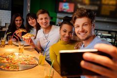 Multiracial friends taking selfie in pizzeria. Stock Photo