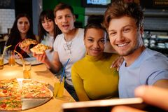 Multiracial friends taking selfie in pizzeria. Stock Photography