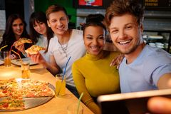 Multiracial friends taking selfie in pizzeria. Royalty Free Stock Image