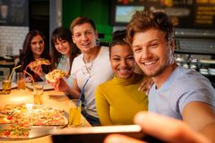 Multiracial friends taking selfie in pizzeria. Royalty Free Stock Images
