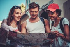 Multiracial friends tourists with map Royalty Free Stock Image
