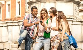 Multiracial friends using mobile smart phone at city tour - Happy friendship concept with student having fun together - Millenial. People on peace love concept royalty free stock image