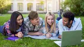 Multiracial friends watching and laughing at video on laptop, students at break royalty free stock image