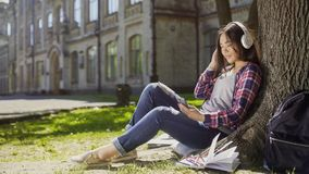 Multiracial girl sitting under tree in headphones, scrolling screen of cellphone Royalty Free Stock Image
