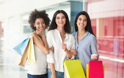 Multiracial girlfriends with colourful bags in shopping center. Happy multiracial girlfriends with colourful bags in shopping center royalty free stock photo