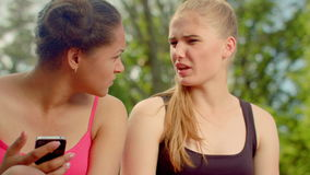 Multiracial girls talking in park. Closeup of multi ethnic women talking. Outdoors. Girlfriends gossiping. Female friends communicate together. Two girls stock footage