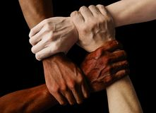 Multiracial group with black african American Caucasian and Asian hands holding each other wrist in tolerance unity love and anti stock image
