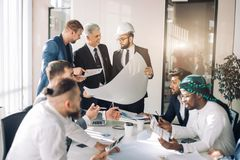 Multiracial group of constructors and architects discussing blueprint at office. royalty free stock photo