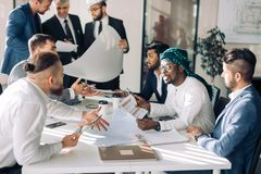 Multiracial group of constructors and architects discussing blueprint at office. stock photos