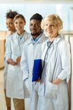 A multiracial group of doctors in lab coats standing in a. Row smiling royalty free stock images