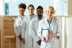 A multiracial group of doctors in lab coats standing. In a row royalty free stock image