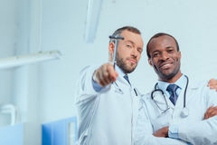 Multiracial group of doctors in medical uniforms in clinic. Portrait of multiracial group of doctors in medical uniforms in clinic Royalty Free Stock Images
