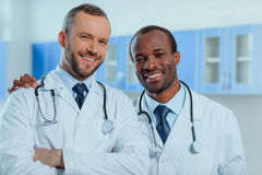 Multiracial group of doctors in medical uniforms in clinic. Portrait of multiracial group of doctors in medical uniforms in clinic Stock Images