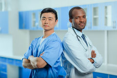 Multiracial group of doctors in medical uniforms in clinic. Portrait of multiracial group of doctors in medical uniforms in clinic Royalty Free Stock Photo