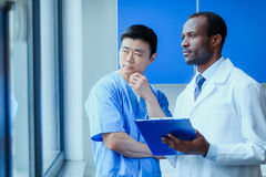Multiracial group of doctors in medical uniforms with folder in clinic. Side view of multiracial group of doctors in medical uniforms with folder in clinic Stock Image