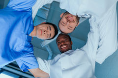 Multiracial group of doctors standing in circle in clinic. Bottom view of multiracial group of doctors standing in circle in clinic Royalty Free Stock Image