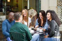 Multiracial group of five friends having a coffee together. Three women and two men at cafe, talking, laughing and enjoying their time. Lifestyle and royalty free stock photo