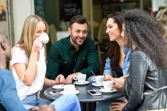 Multiracial group of five friends having a coffee together Royalty Free Stock Images
