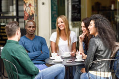 Multiracial group of five friends having a coffee together. Three women and two men at cafe, talking, laughing and enjoying their time. Lifestyle and Stock Images