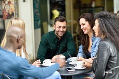 Multiracial group of five friends having a coffee together. Three women and two men at cafe, talking, laughing and enjoying their time. Lifestyle and royalty free stock photos