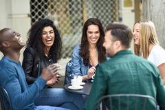 Multiracial group of five friends having a coffee together. Three women and two men at cafe, talking, laughing and enjoying their time. Lifestyle and Stock Photo
