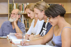 Multiracial group of four people studying library royalty free stock image