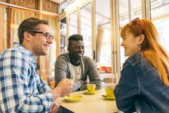 Multiracial group of friend in a coffee bar Stock Images