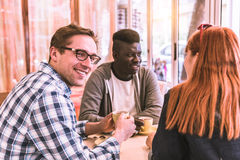 Multiracial group of friend in a coffee bar Royalty Free Stock Photos