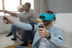 Multiracial group of friends having fun trying on 3D virtual reality goggles. stock photography