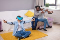 Multiracial group of friends having fun trying on 3D virtual reality goggles. stock photos