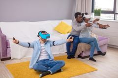 Multiracial group of friends having fun trying on 3D virtual reality goggles. royalty free stock image