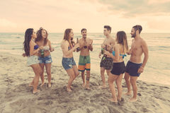 Multiracial group of friends having a party on the beach royalty free stock photos