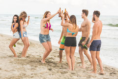 Multiracial group of friends having a party on the beach. Dancing and drinking beer. They are teenagers, four girls and three boys, standing just next to the stock photo