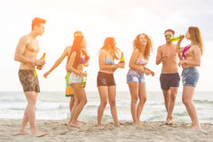Multiracial group of friends having a party on the beach. Dancing and drinking beer. They are teenagers, four girls and three boys, standing just next to the stock image
