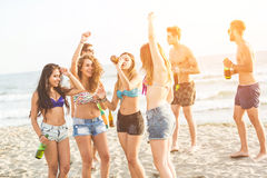 Multiracial group of friends having a party on the beach. Dancing and drinking beer. They are teenagers, four girls and three boys, standing just next to the stock images