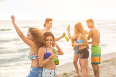 Multiracial group of friends having a party on the beach Stock Images
