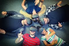 Multiracial group of friends playing on vr glasses indoor - Virtual reality concept with young people having fun together. Connecting with headset goggles stock photography