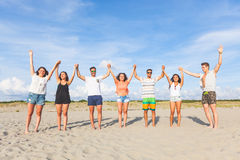 Multiracial group of friends with raised hands on the beach Royalty Free Stock Photography