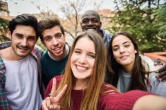 Multiracial group of friends taking selfie Stock Photos