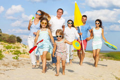 Multiracial group of friends walking at the beach. Multiracial group of friends with children running at the beach stock images