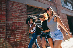 Multiracial group of friends walking down the city street. Three young women walking outdoors on road Royalty Free Stock Photography