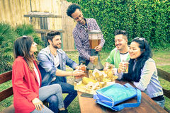 Multiracial group of happy friends eating and toasting at bbq Stock Photography